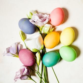 ピンクのマーブルの背景に花と卵、イースターの挨拶のためのコピースペース