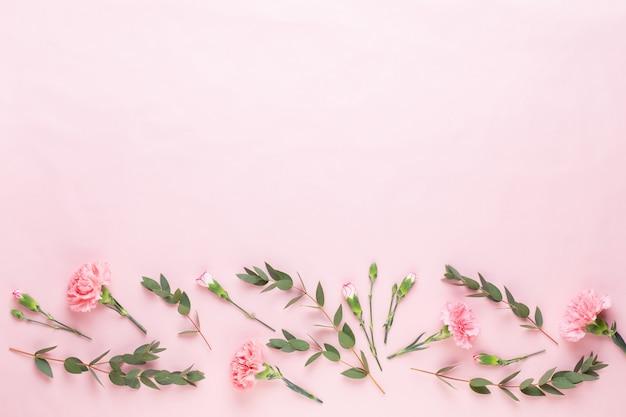 花とeucaaliptusの構成。白い背景の上の様々な色とりどりの花で作られたパターン。フラットレイスティルライフ。