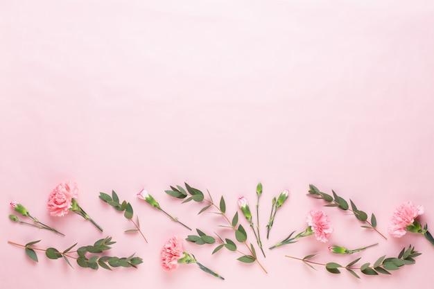 白い背景の上に様々な色とりどりの花で作られた花とユーカリの組成物。フラットレイスティルライフ。