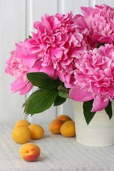 テーブルの上の花と果物。ピンクの牡丹とアプリコットの花束。