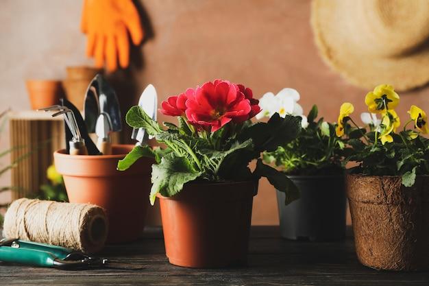 花と木製のテーブルの上の園芸工具をクローズアップ