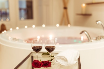 Flowers and glasses of drink near spa tub with water and burning candles on edges
