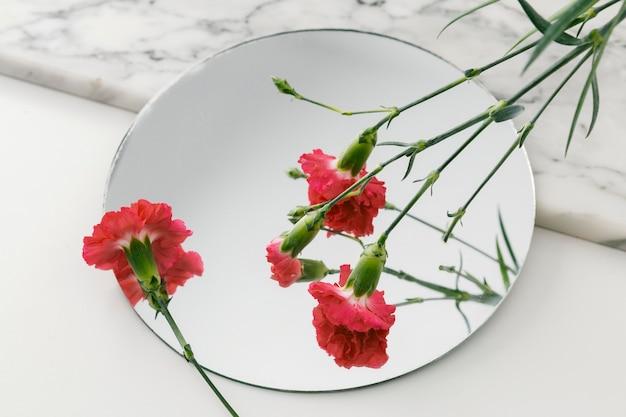 花とテーブルの上の鏡