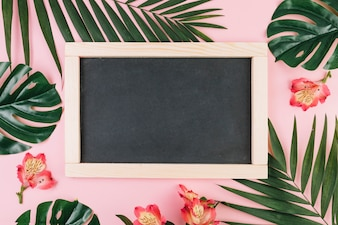 Flowers and palm leaves around blackboard