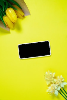 花と電話。背景に黄色のモノクロスタイリッシュでトレンディな構成。上面図、フラットレイ。周りのいつものものの純粋な美しさ。広告のコピースペース。休日、食べ物、ファッション。