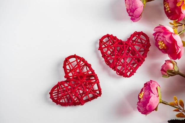 バレンタインデーのための白い背景の花と赤いハート。 2つの赤いハートと白い背景の上の繊細なピンクの花