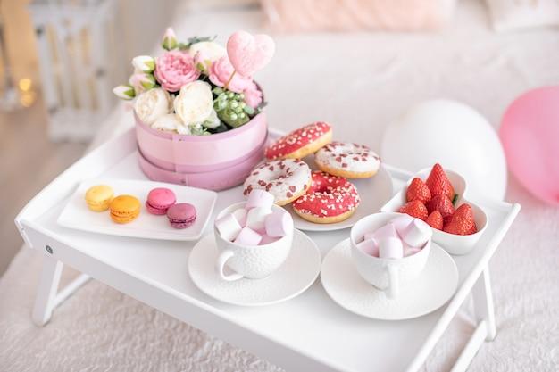 Цветы и сладости на белом столе и воздушные шары на белой кровати. подарок ко дню матери