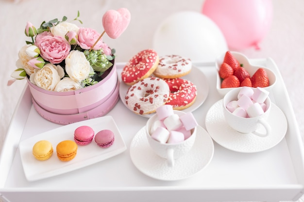 白いテーブルの上に花とお菓子、白いベッドの上に風船。母の日のギフト