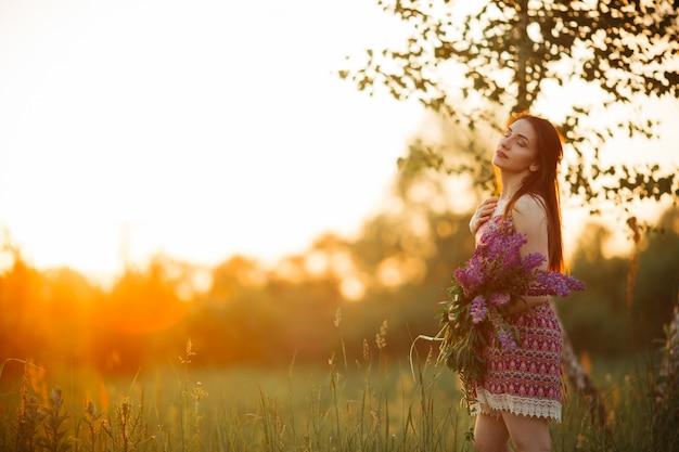 Цветы и женщина ладонь в поле. освещенное вечернее солнце