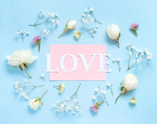 花と水色の背景の上面図の愛という言葉