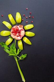 Цветы сделаны из граната, яблок и сельдерея на черной поверхности.