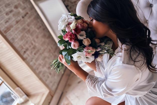 花は完璧です。ソファに座って花束の匂いを嗅ぐシルクバスローブの美しい若い女性