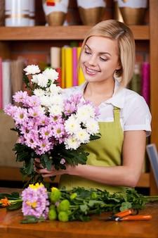 Композиция из цветов. красивая молодая женщина со светлыми волосами в фартуке, аранжировка цветов и улыбка