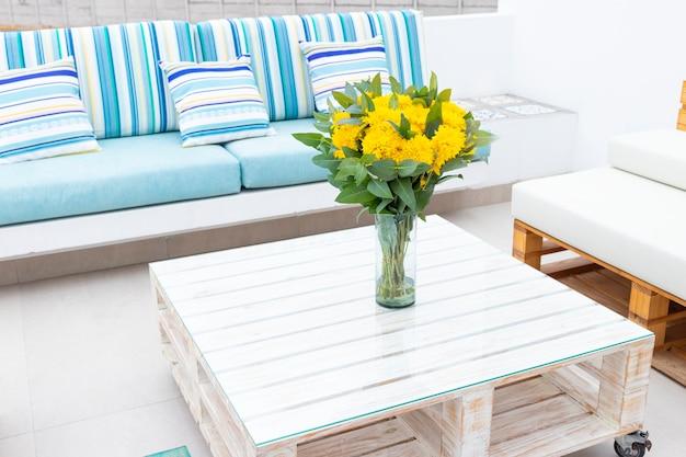 Композиция из цветов на столе на открытом воздухе на террасе дома