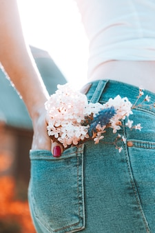 Flowers in the back pocket of blue jeans, a girl with red manicure