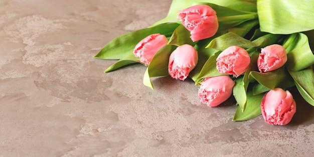 Цветы. баннер с букетом розовых тюльпанов на сером мраморном фоне. вид сверху с copyspace. международный женский день, пасха, день святого валентина, весенняя концепция.
