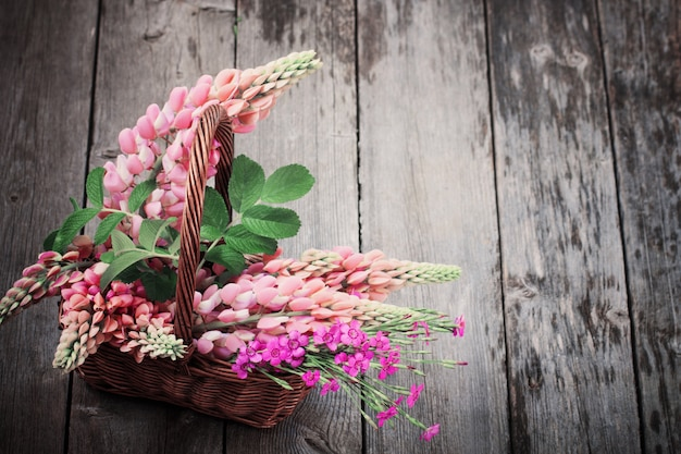 Flowers in basket on old background