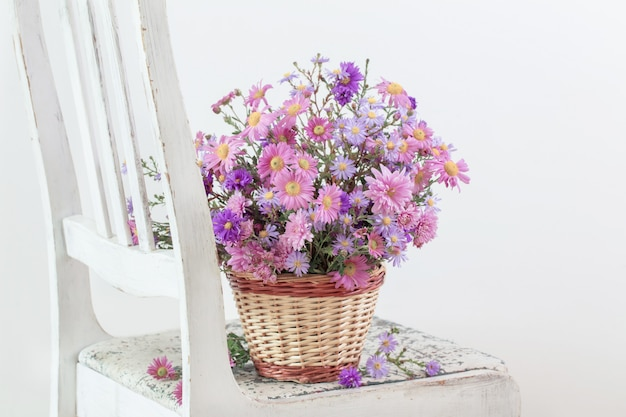 Flowers in basket on old white chair
