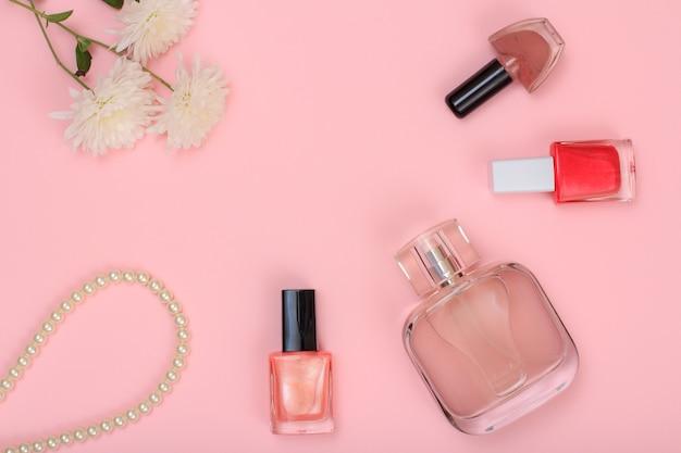 花、ビーズ、香水のボトル、ピンクの背景にマニキュアのボトル。女性の化粧品とアクセサリー。上面図。