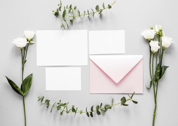 テーブルの上の結婚式の招待状の横にある花