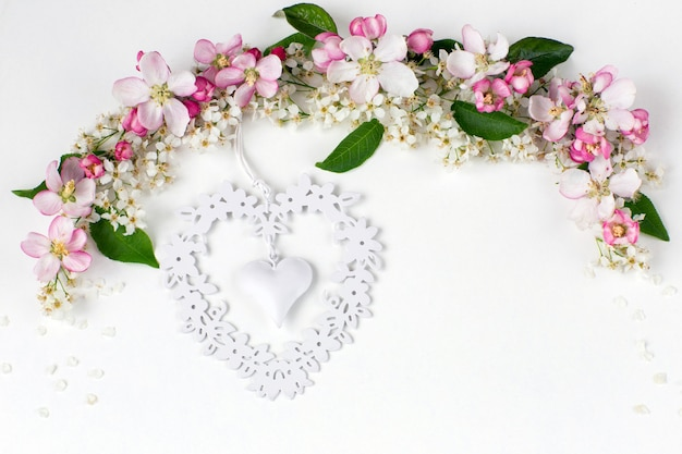 Flowers of the bird cherry and the apple tree are lined with an arch and a white tracery heart