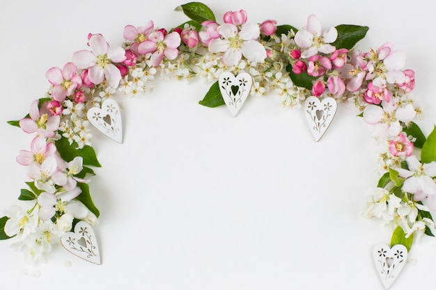 Flowers of a bird cherry and apple trees are lined with an arch and decorative white hearts