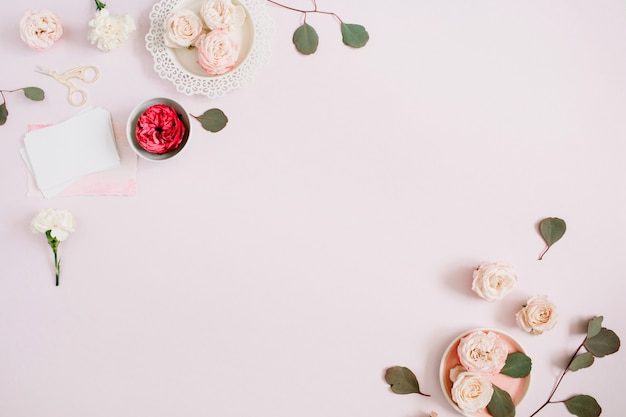Flowers border frame made of beige and red roses and white carnation on pale pastel pink