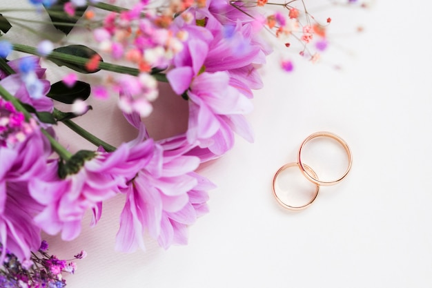 Flowers bouquet beside engagement rings