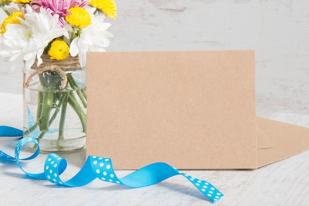 Flowers bouquet in a jar vase with card note, envelope and blue ribbon on a white wood rustic background