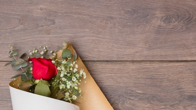 Flowers bouquet in pack paper on wooden table