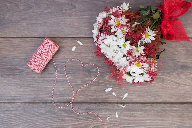 Flowers bouquet with heart from rope on wooden table