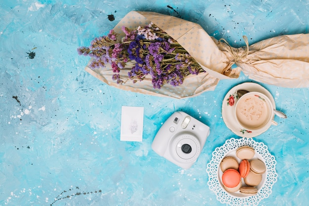 Flowers bouquet with instant camera, coffee cup and cookies
