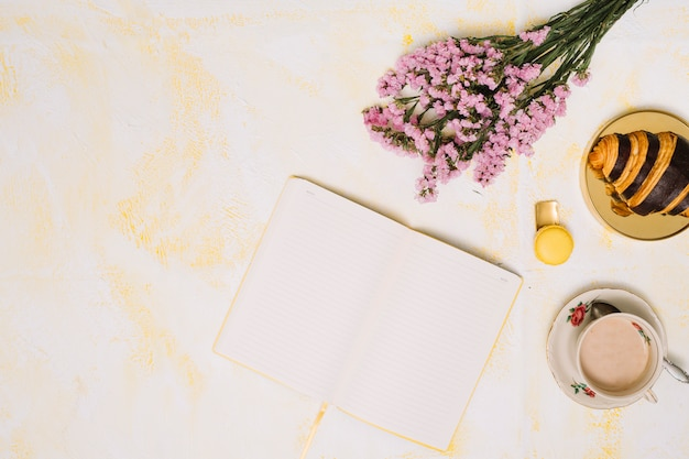 Flowers bouquet with notebook, coffee and croissant on table