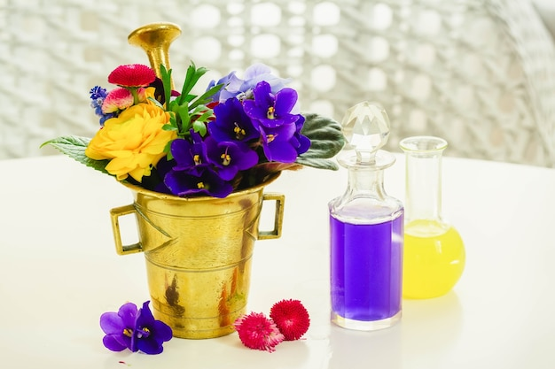 Flowers, brass mortar and bottles of potions, floral science and herbal medicine