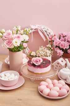 Flowers and cake on pink background