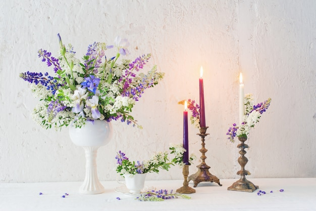 Flowers and candles on background white wall