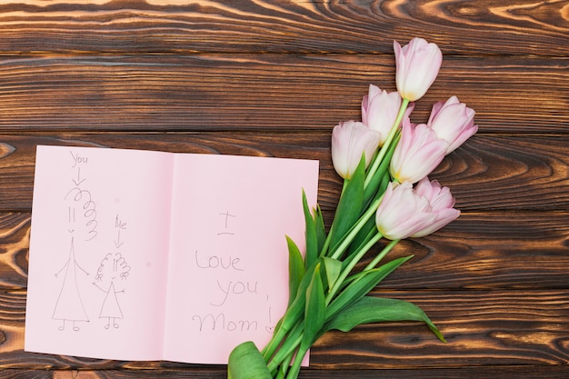 Flowers and child drawing with text i love you mom on wood table