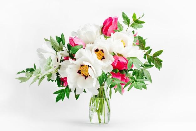 Композиция цветов. красивый букет из белых пионов и розовых тюльпанов в стеклянной вазе на белом фоне.