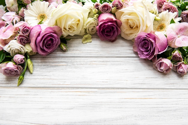 花の構成。白い木製の背景にピンクの花で作られたボーダー。フラットレイ、上面図、コピースペース