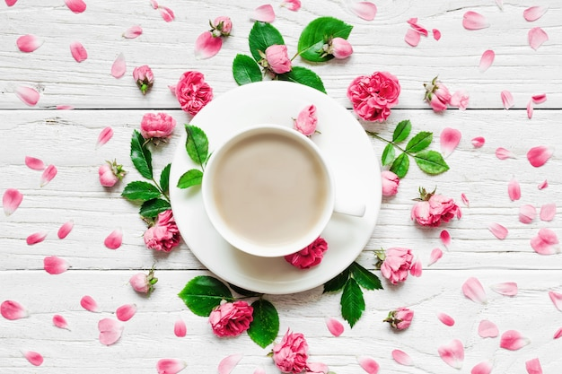 Flowers composition. frame made of fresh rose flowers with cup of cappuccino on white wooden background. flat lay