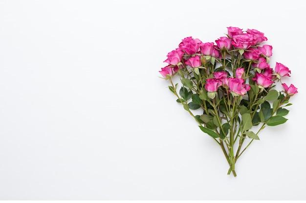 花の構成。白い木製の背景に赤いバラで作られたフレーム。フラットレイ、上面図、コピースペース。