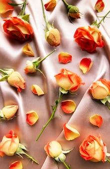 シルクの背景に赤いバラと葉で作られた花の構成フレーム