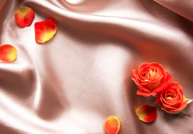 Flowers composition frame made of red  roses and leaves on beige silk background space
