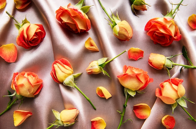 Flowers composition. frame made of red  roses and leaves on silk background. top view, flat lay, copy space