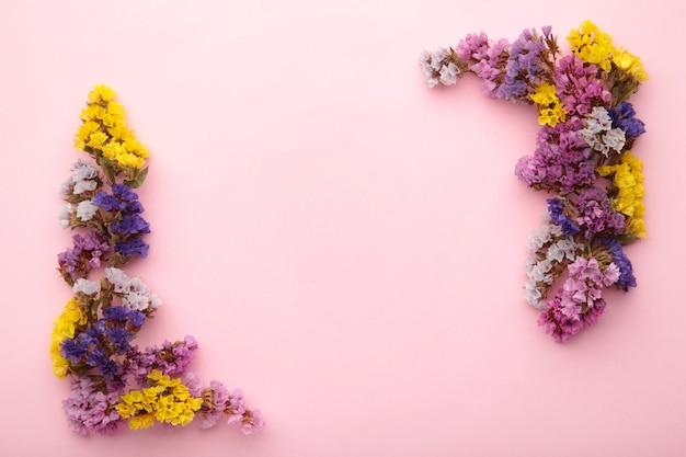 花の構成。パステルピンクの背景にカスミソウの花。フラットレイ、上面図、コピースペース。春