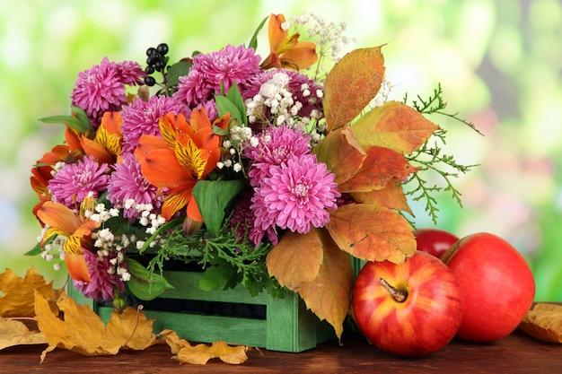 Композиция цветов в ящике с яблоками на деревянном столе