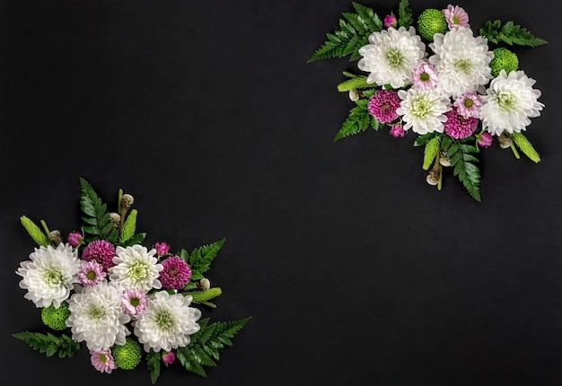 黒の背景に分離された色とりどりの花菊の花の構成。菊の花の夏の花輪。フラットレイ。