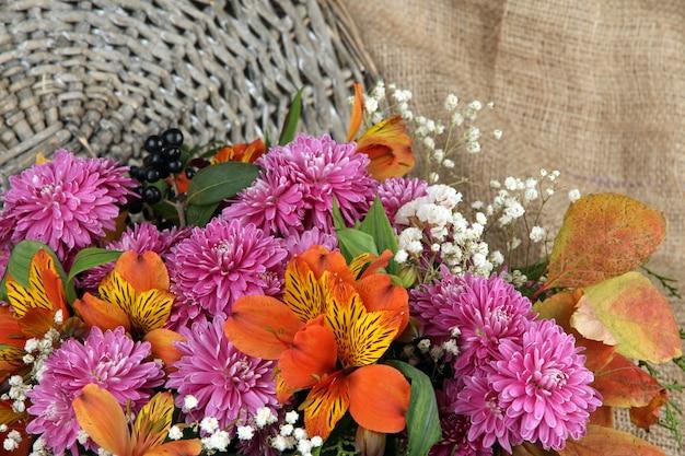 枝編み細工品の背景に花の組成
