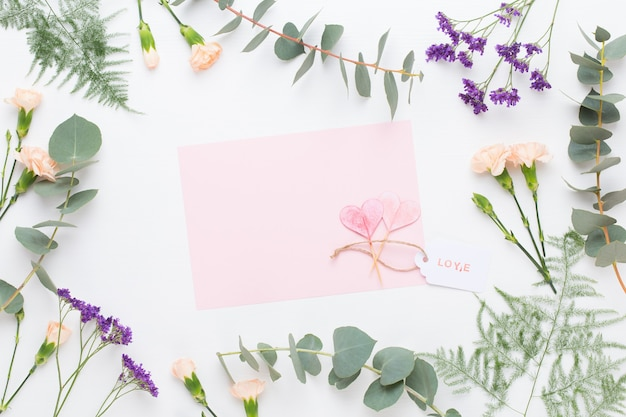 꽃 조성. 종이 빈, 카네이션 꽃, 파스텔 배경에 유칼립투스 가지. 평면 평신도, 평면도.