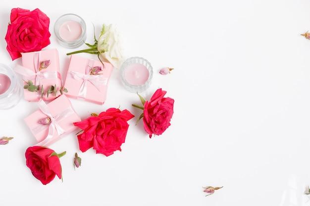 꽃 구성입니다. 흰색 바탕에 분홍색 선물과 빨간 장미 꽃. 평면도, 평면도, 복사 공간. 생일, 어머니, 발렌타인, 여성, 결혼식 날 컨셉입니다.